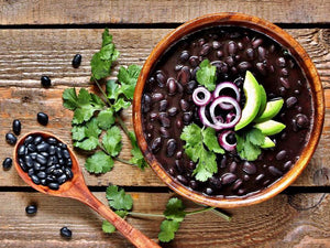 Bowl of authentic black beans topped with cliantro, onion, and avocado