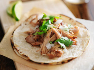 Carnitas on a grilled corn tortilla topped with cilantro and onion