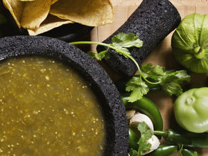 Roasted green salsa in mortar bowl with pestel, cilantro, corn chips, tomatillos, and peppers on the side