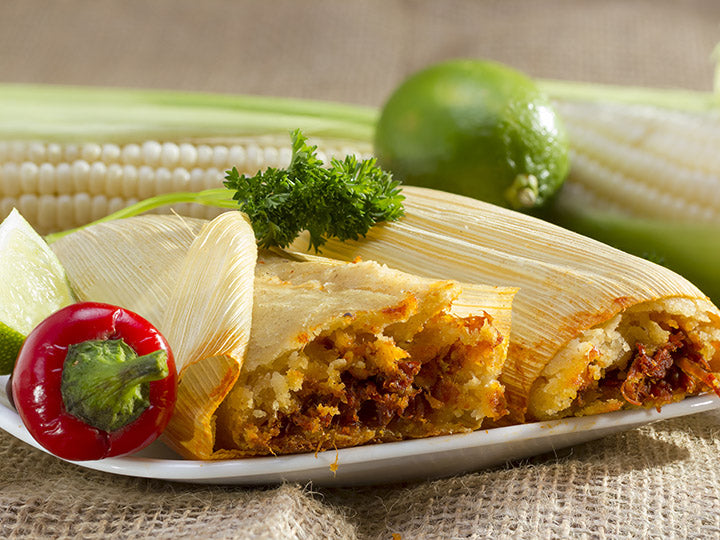 Plate of red pork tamales garnished with corn, lime, parsley, and red pepper
