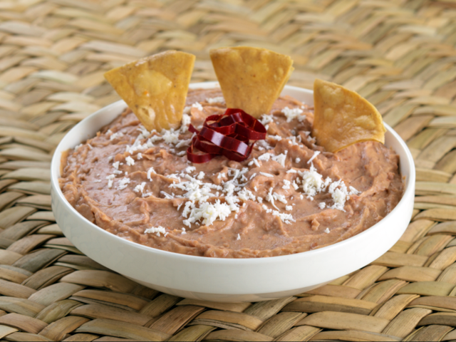 Refried beans in a white bowl garnished with chips and queso fresco
