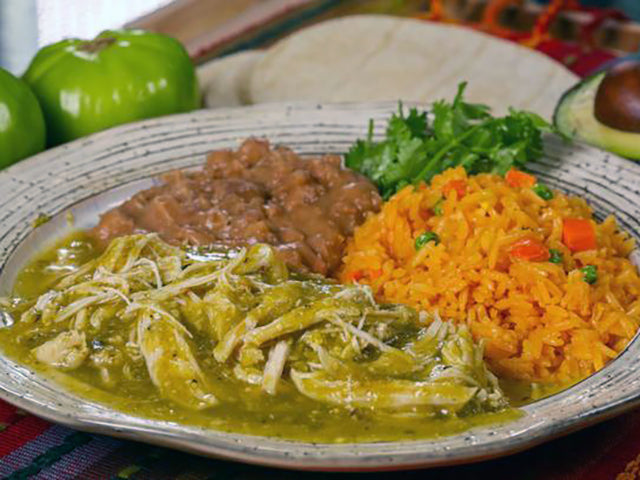 shredded chicken in roasted salsa verde on a plate with beans and rice