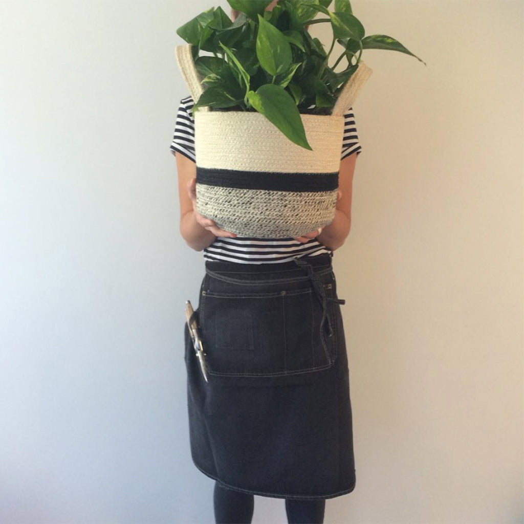 Woman holding a plant wearing black denim waist apron
