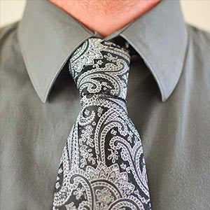 Man wearing a black paisley tie with a gray dress shirt
