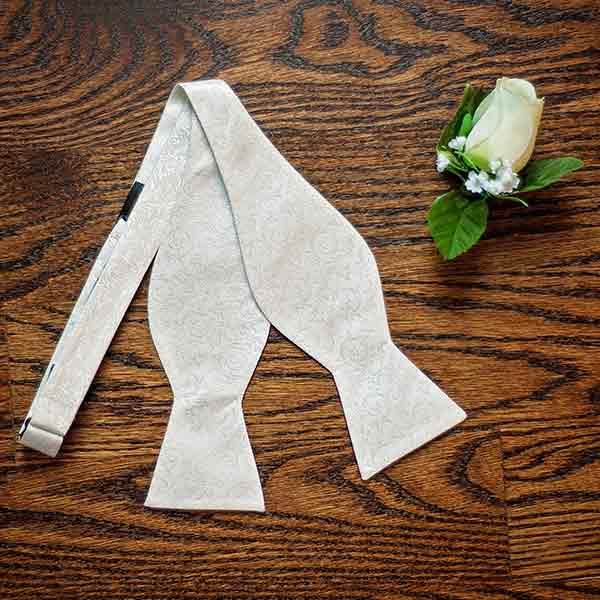 Ivory self-tie bow tie with textured floral pattern and boutonniere