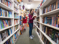 Girls reading in aisle of books