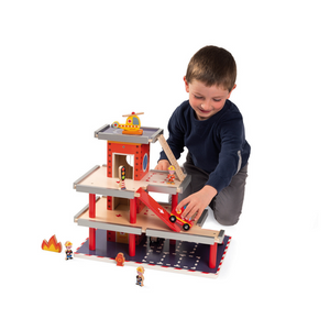 Child playing with wooden fire station