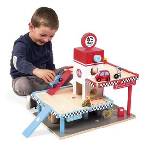 Child playing with wooden gas station