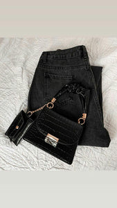 Black slouchy women jeans and a black top handle shoulder bag
