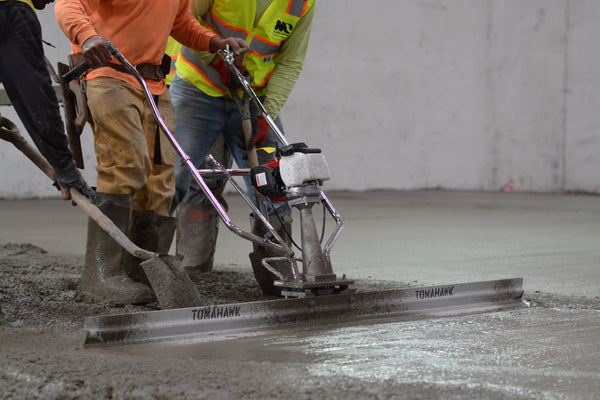Construction worker using a Tomahawk power screed