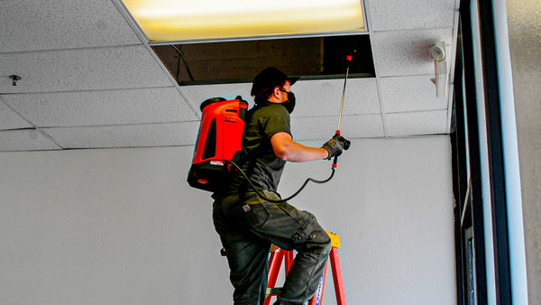 Man spraying pesticides with a Tomahawk Power 4.75 Gallon Battery Powered Backpack Sprayer for Pest Control