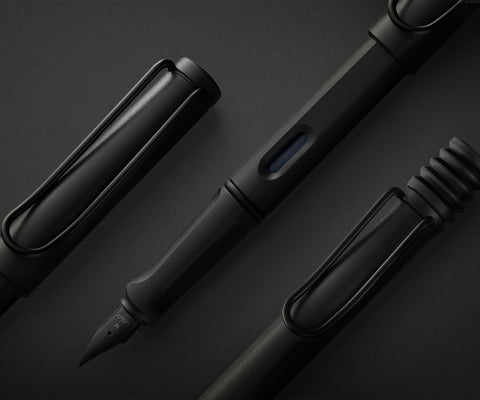 LAMY safari 2018 Special Edition All Black, with the completely-black fountain, rollerball and ballpoint pens laid out on a black surface