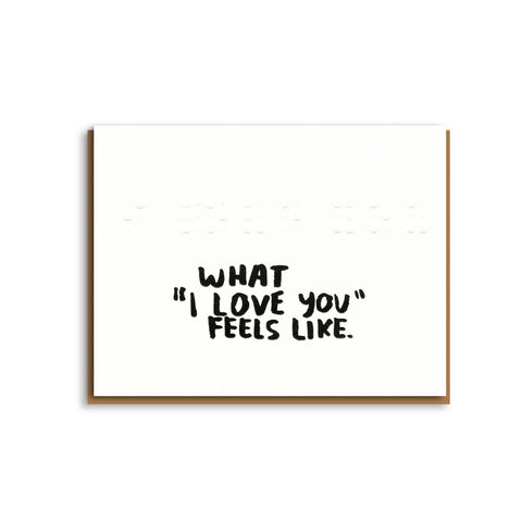 "A white rectangular greeting card with the words ""What 'I Love You' Feels Like"" written on the front in a loose black font"