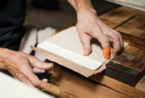 [img: a stack of papers being bound and cut for a notebook, held on a work-bench by two hands]