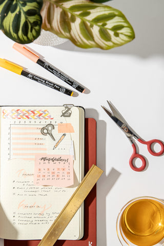 A bustling bullet journal laid open on a desk with scissors, ruler, markers and a cup of tea