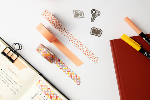 A dot grid bullet journal notebook with washi tape, clips and brush markers spread around it