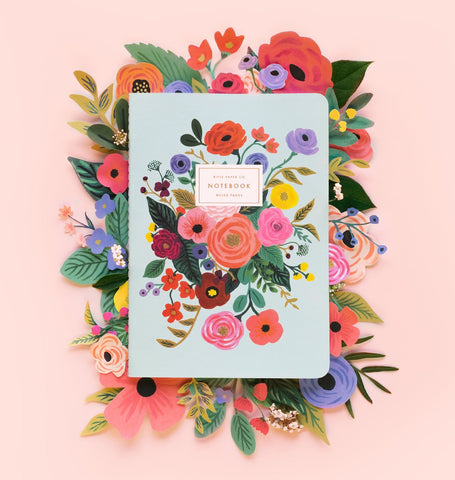 A soft cover Rifle Paper Co. notebook with a floral design on its pale blue cover, on a bed of papercraft flowers in the same style as the notebook art