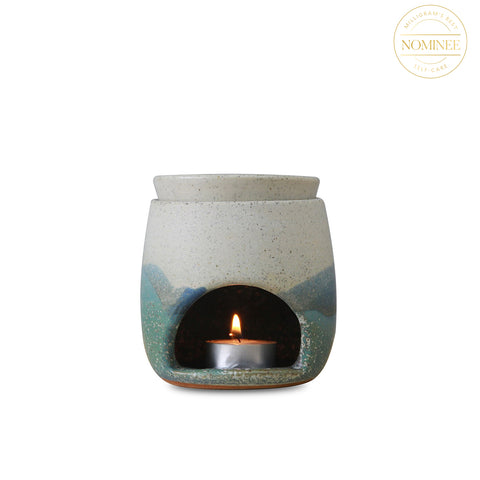 A small cylinder of cream and blue ceramic with rounded edges, with an arch-shaped opening holding a tea light candle
