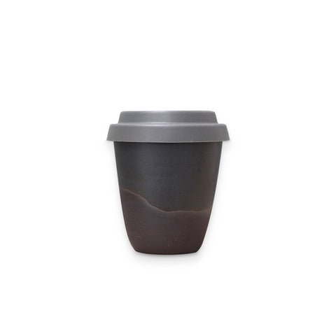 Arcadia Scott Ceramics' Travel Tumbler in Noir finish, the gently curved clay cup all dark greys and soft blacks with a pale grey silicon lid