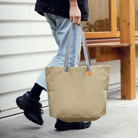 A person holding a Market Tote in Khaki by the handles as they walk