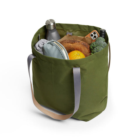 Bellroy's Market Tote in Ranger Green fabric, filled with a loaf of bread, a water bottle and lots of veggies