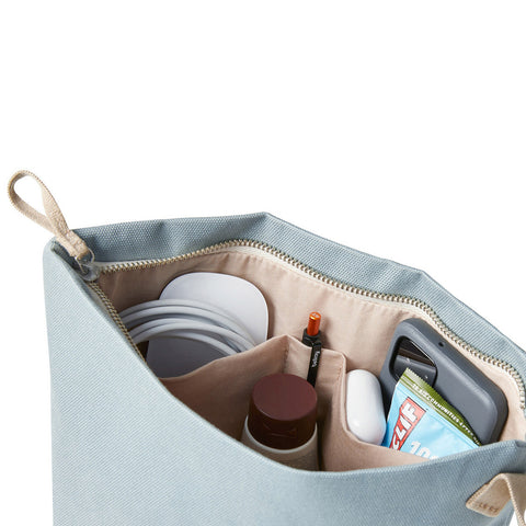 An inside view of Bellroy's Standing Pouch Plus in Smoke Blue, showing internal pockets holding a phone, cables, mouse, pen, AirPod case and more