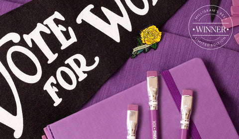 Blackwing's Volume XIX pencils with a purple finish and erasers laid on top of a matching purple notebook next to a black pennant flag with text reading Votes For Women