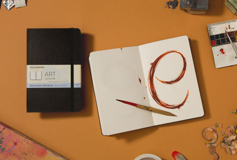 A closed Moleskine Art Watercolour Notebook sits on a bench next to an open version with a vibrant, dramatic 'e' painted in watercolour on one plain page.