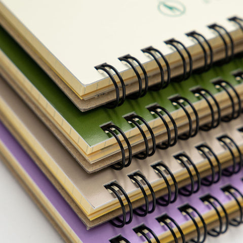 A close-up of four spiral-bound Rollbahn notebooks from the top-left corner, stacked vertically on top of each other in a loose pile