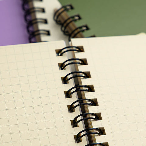 A close-up shot of a Rollbahn notebook's grid pages, which are a creamy colour with pale 5mm square grid layout bound with a black spiral binding