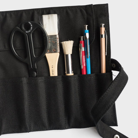 Delfonics Canvas Roll Pencil Case | Milligram [img: a black piece of canvas lays flat on a white surface, with pens, brushes and scissors held in its slim vertical pockets. A strip of canvas with a push-stud hangs off one side of the canvas piece]