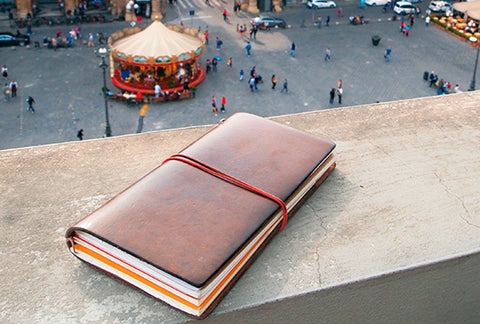 A Traveler's Notebook, full of memories, sits on a ledge overlooking a busy town square