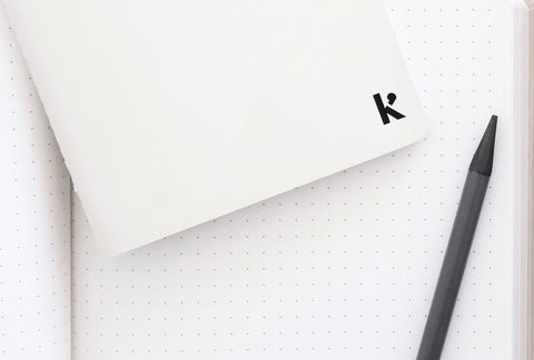 A open Karst notebook shows its white pages with dot grid layout, and a Karst Woodless Pencil rests on top of the page. Another notebook, this one closed, rests on top of the other.
