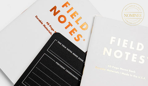 Field Notes Group Eleven notebooks, featuring white covers with the Field Notes logo in silver and copper