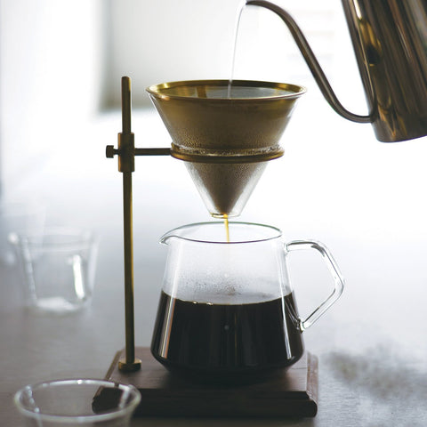 Kinto's Slow Coffee Style Brass Brewer Set sat on a bench, brewing a batch of dark, rich coffee