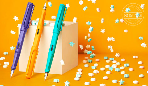 LAMY safari candy special edition fountain pens in Violet, Mango and Aquamarine stood on a yellow background with confetti