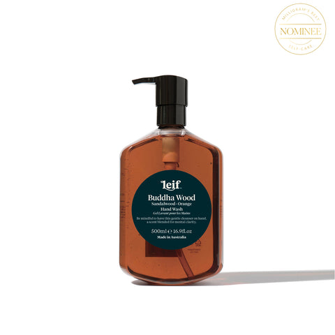 Leif's Buddha Wood hand wash, in a translucent bottle with dark amber liquid inside behind a circular, deep green label with Leif printed in white