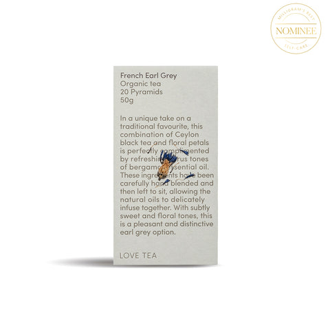 Love Tea French Early Grey Tea, in a soft stone-coloured rectangular box with dense black type with an image of a dried cornflower blossom superimposed