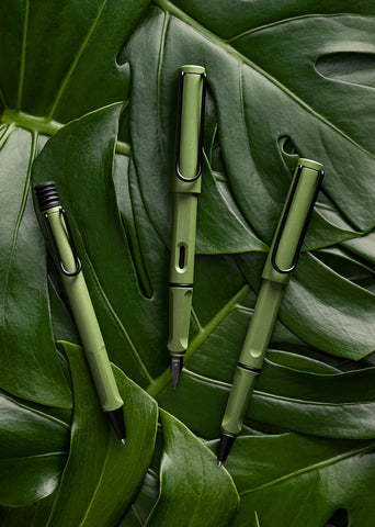 safari Anniversary pens in savannah green finish laid on a bed of monstera leaves