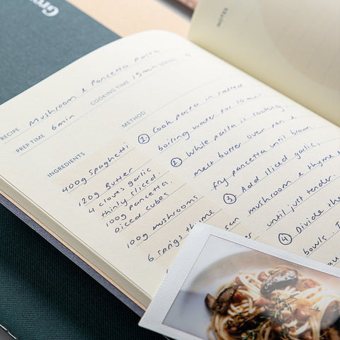 A Studio Milligram Cook Life Journal with a handwritten recipe for mushroom and pancetta pasta