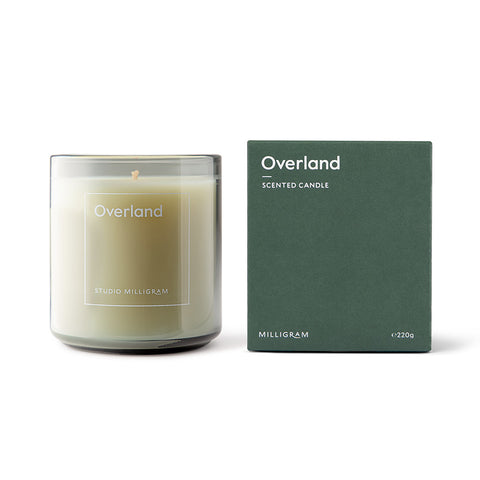 Studio Milligram's Overland Scented Candle [img: a candle in a translucent glass cylinder stands next to a green cubic box with 'Overland' written on the front in a subtle white typeface]