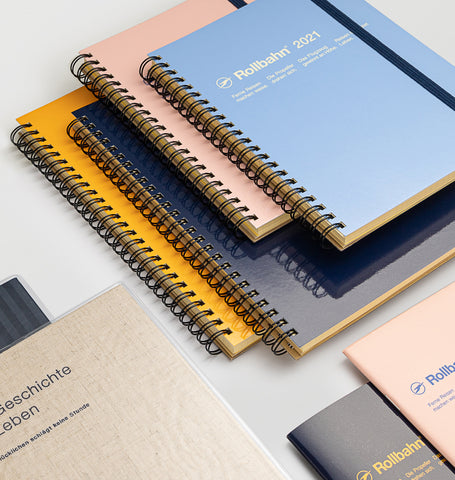 A stack of Delfonics 2021 Rollbahn diaries with yellow, blue, pink and dark blue covers