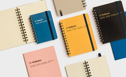 [img: a flat lay of Rollbahn notebooks with yellow, pink, blue and black covers]