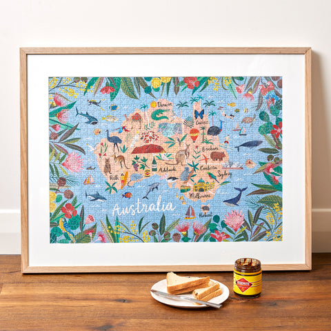 "Journey of Something ""Australia"" puzzle, framed, with a jar of Vegemite and toast triangles in front ofit"