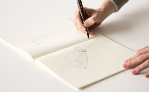 A Midori notebook lays flat on a white surface, with a hand holding a pen hovering over the page and a loose sketch of a person in progress