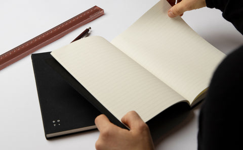 A person holding a Studio Milligram notebook open to show its ruled pages