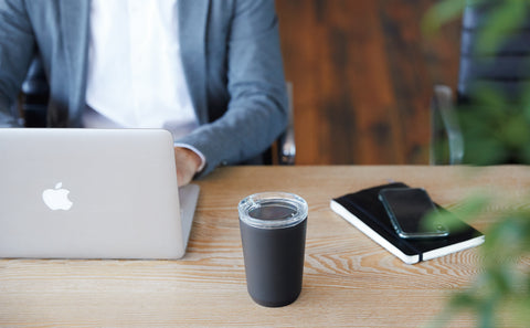 Kinto's To-Go Tumbler in Black sitting on a cafe table next to a laptop