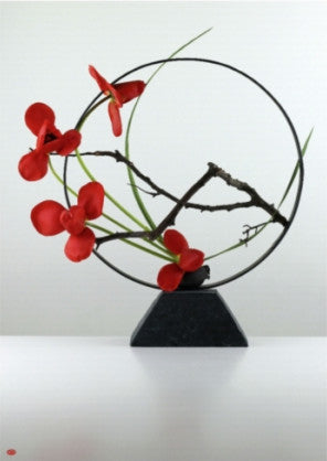 'Tsuboniwa', an ikebana arrangement made with tulip, cordyline leaf and cast iron pot. A slim black ring stands upright on top of the trapezoidal cast iron pot, with a small branch reaching from right to left. Four flowers mark the lower left edge of the circle, stark red against the black metal