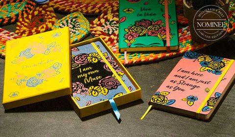 The three Moleskine Frida Kahlo notebooks, with pink, green and blue covers featuring Frida-style floral designs