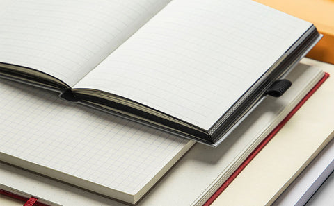 A stack of different notebooks, piled on top of each other with their pages open